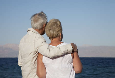 retired couple: A retired couple lost in their thoughts as they watch the ocean Stock Photo