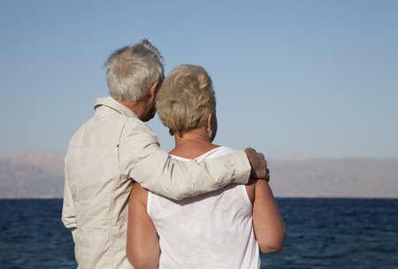 Een gepensioneerd echtpaar verloren in hun gedachten als ze kijken naar de oceaan