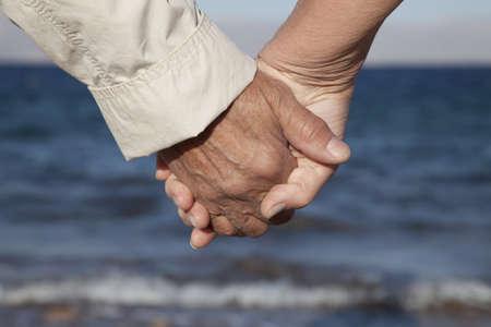 海に対して手を繋いでいるロマンチックな年配のカップルの背面をクローズ アップ 写真素材