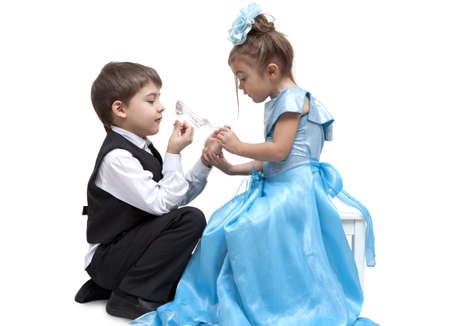lady slipper: Little boy fitting a glass slipper onto a beautiful little girl