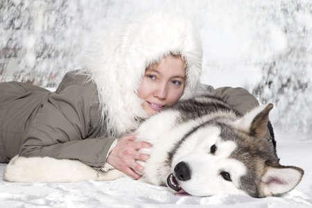Vijf maanden oude malamute pup met jonge blanke vrouw Stockfoto
