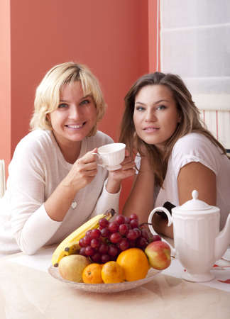 Happy smiling mother and daughter have breakfast. Looking at camera photo