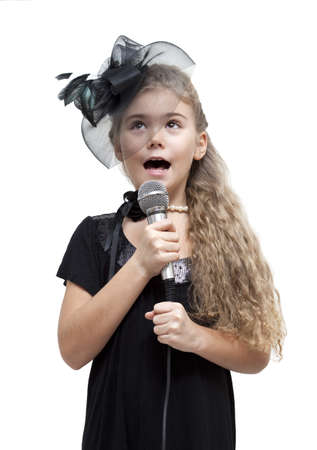 Cute little girl singing into a microphone on a white background photo