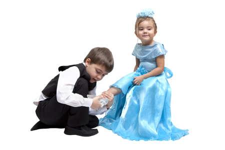 Jongetje aanbrengen van een glazen muiltje op een klein meisje Stockfoto