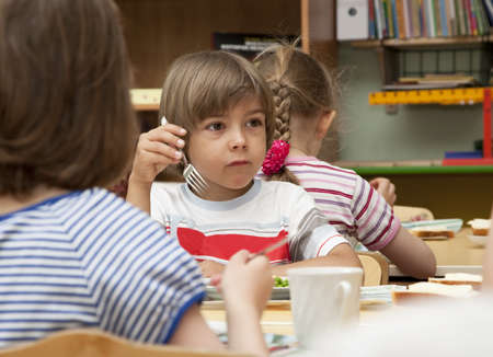 Little boy has a lunch in the kindergarten Stock Photo - 13567281