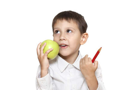 one boy only: cute boy with green apple and red pencil isolated on a white background