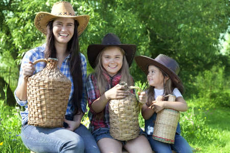 Portrait of three Caucasian girls in cowboy hats in a garden photo