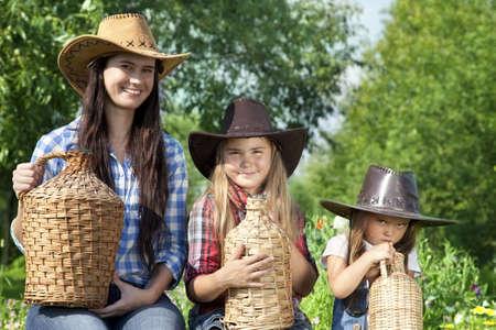 demijohn: Portrait of three Caucasian girls in cowboy hats in a garden Stock Photo