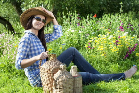 demijohn: Portrait of Caucasian young woman with demijohn in a garden Stock Photo