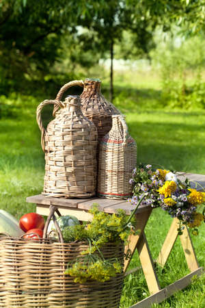demijohn: Rural still life with demijohns and basket of vegetables  Stock Photo