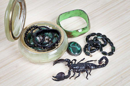 Emperor Scorpion with onyx jewelry box, malachite brooch and black necklace photo