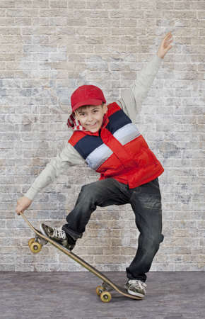 Skater boy crouching on his skateboard in front of brick wall. photo
