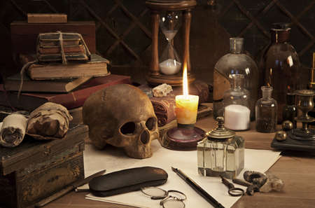 Alchemy still life with skull and burning candle