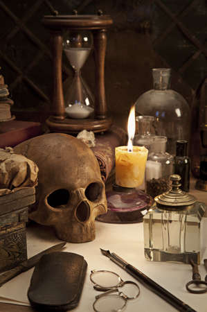 gothic revival style: Alchemy still life with skull and burning candle