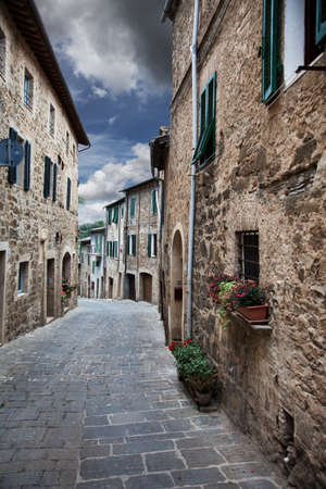 'dark ages': Ancient alleyway with dramatic sky   Montalcino  Tuscany, Italy