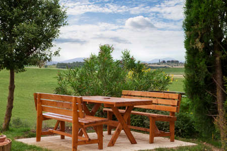 frontyard: Wood picnic table and benches in countryside Stock Photo