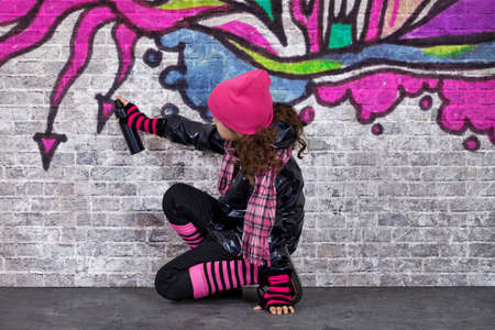 Teenager girl painting a graffiti on a wall Stock Photo