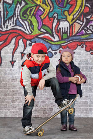 Skater boy and little girl in front of the wall covered with graffiti photo