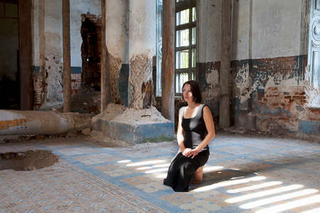 blasted: Young woman praying in old Abandoned Church