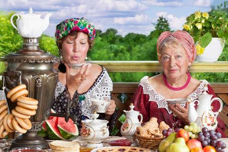 Women drinking tea outdoors  Kustodiev Russian artist style, beginning of the last century photo