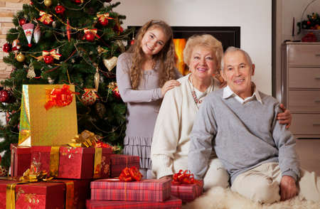 Senior couple with granddaughter sitting in front of Christmas tree smiling at camera  photo