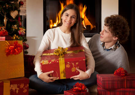 young happy couple near fireplace with Christmas gifts photo