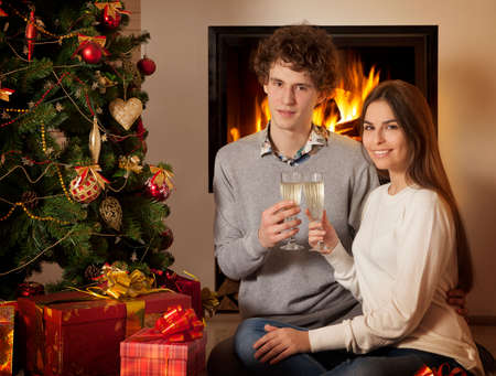 happy young couple with glasses of wine in Christmas interior Stock Photo - 24611746