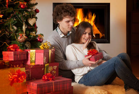 Couple Christmas lifestyle, young woman receiving her gift Stock Photo - 24611748