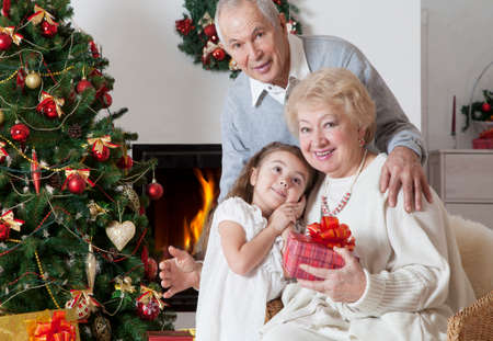 Senior couple with granddaughter celebrating Christmas in front of fireplace photo