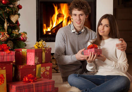 young couple with Christmas gifts  in front of fireplace Stock Photo - 24611770