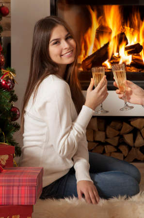 Pretty young woman with glass of wine in front of fireplace  photo