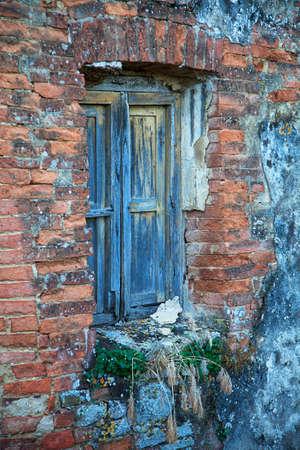 ramshackle: Blue window of abandoned building. Tuscany, Italy  Stock Photo