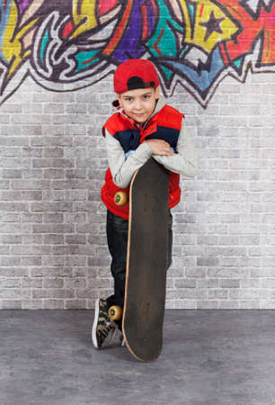 skater boy: Skater boy with his skateboard in front of brick wall. He is looking at camera with a smile