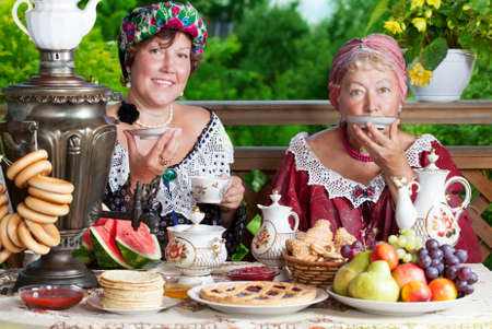 Two mature women from the Victorian era having a cup of tea  photo