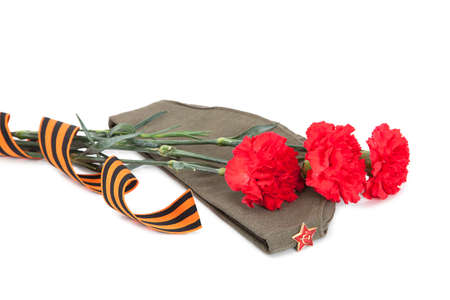 may 9: Carnations with George ribbon and field cap  on white background  Stock Photo