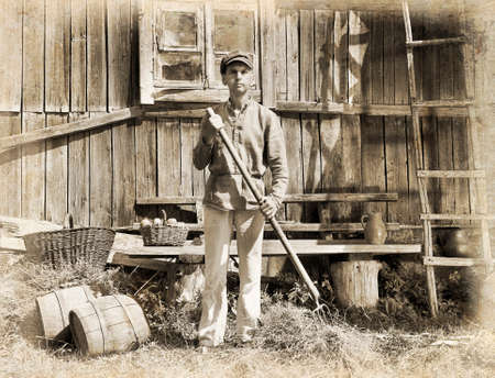 emulation: Male farmer holding a pitchfork. Intentional 1900s style post processing emulation.  Stock Photo