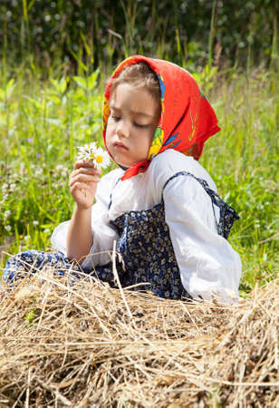 oxeye: Outdoor portrait of a little girl with oxeye daisy flowers in her hands  Stock Photo