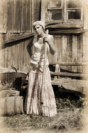 emulation: Woman holding a pitchfork. Intentional 1900s style post processing emulation.  Stock Photo