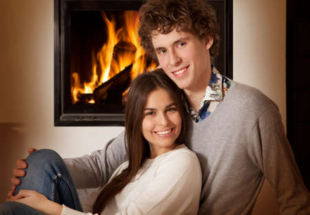 fireplace family: Portrait of lovely couple in front of a fireplace,  looking at camera