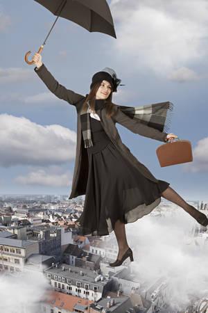 若い女性はメリー ・ ポピンズのように傘で飛ぶ