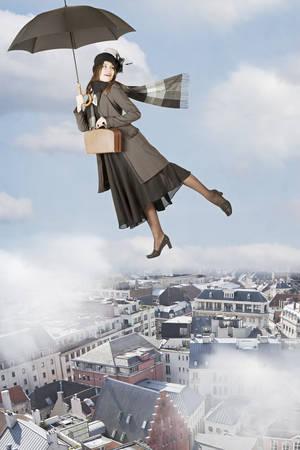 Mary Poppins vliegt op een paraplu over de stad Stockfoto