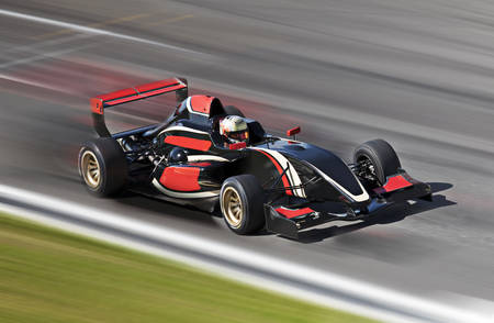 Formula one race car on speed track with motion blur photo