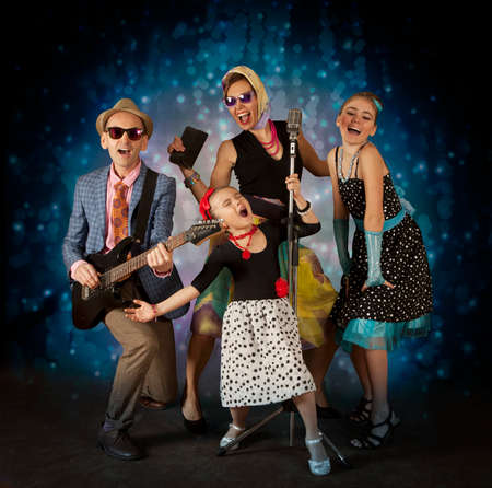 rockabilly: Rockabilly family band having fun playing music and posing with vintage microphone - 1950s style Stock Photo