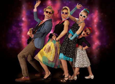 rockabilly: Rockabilly family band having fun posing with guitar and dancing  in 1950's style clothing