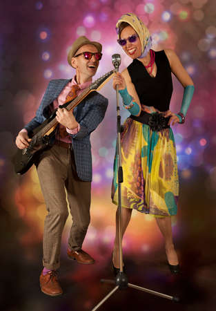 Rockabilly couple having fun playing the guitar and singing on a colorful background with glowing lights photo