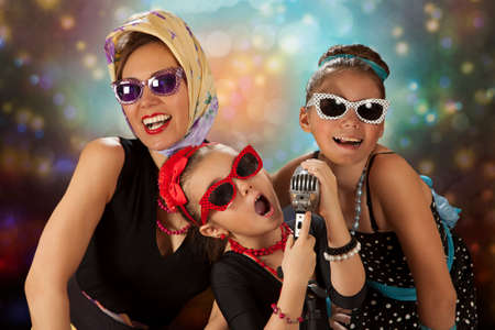 Rockabilly woman with her tow daughters having fun posing with vintage microphone in 1950's style clothing photo