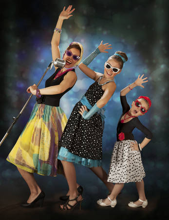 Rockabilly woman with her daughters singing in 1950's style clothing on a colorful background with glowing lights photo