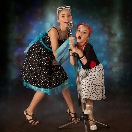 square dancing: Rockabilly girls singing and posing with vintage microphone in 1950's style clothing Stock Photo