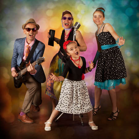 Rockabilly family band playing music and singing on a black background with glowing lights