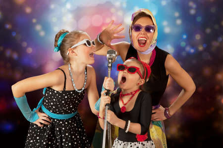 white rock: Rockabilly woman with her daughters having fun posing with vintage microphone in 1950's style clothing Stock Photo